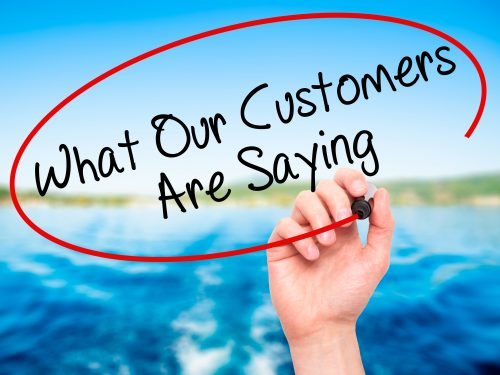 Man Hand writing What Our Customers Are Saying with black marker on visual screen. Isolated on nature. Business, technology, internet concept. Stock Photo