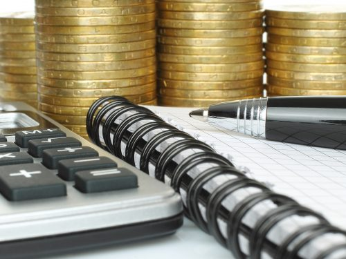Stationery with stack of coins close-up